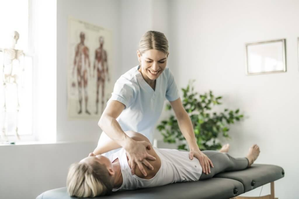 Modern rehabilitation physiotherapy worker with woman client