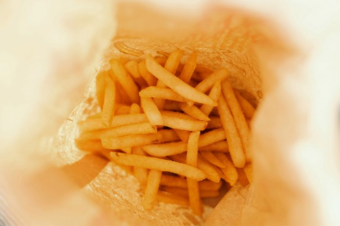 A photo of a a bunch of French fries at the bottom of a bag. Can fried food like this lead to migraines? A new study looks at the issue.