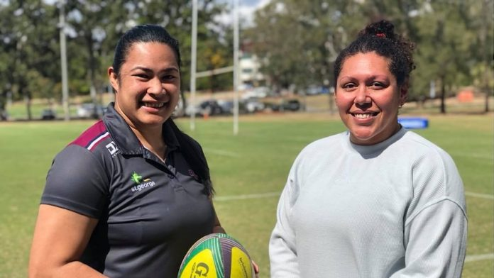 Alisi Qalo-Wilson (left) and Liz Patu (right) standing side by side. Alisi is holding a yellow rugby ball.