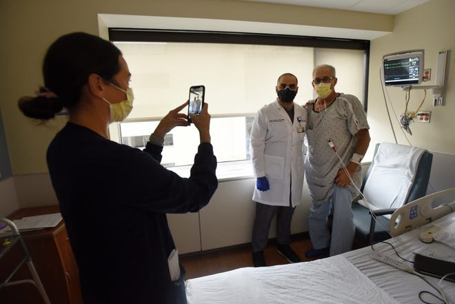 Casey Brooks, left, a nurse instructor at the 6th North Medical Progressive Care Unit at Beaumont Hospital, takes a photo of Dr.  September 21, 2021 in Royal Oak, Mich.  Elezi had asked Aljassem for a portrait.