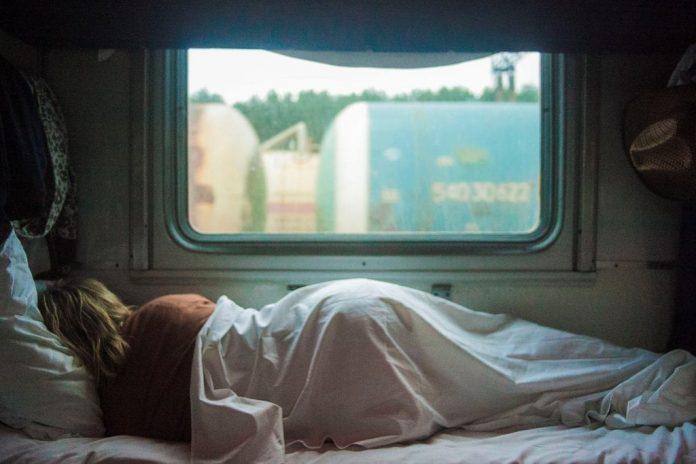 Woman sleeping in front of window in daylight; image by Kalegin Michail, via Unsplash.com.